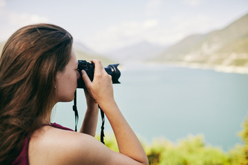 Young tourist Girl taking pictures of mountains and lake. Georgia. Summer. August.