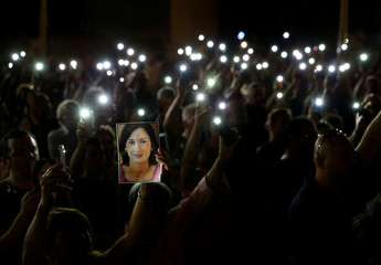 People hold up photos of assassinated anti-corruption journalist Daphne Caruana Galizia and torches on mobile phones during a vigil to mark eleven months since her murder in a car bomb, in Valletta