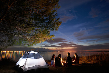 Back view of tourists, girls and boy having a rest on lake shore around compfire at tent on smooth water surface and blue evening sky with first stars at sunset background. Tourism and camping concept