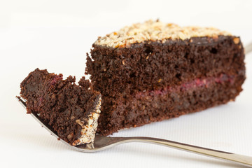 One slice of chocolate cake filled with jam on white background. One bite is on fork.