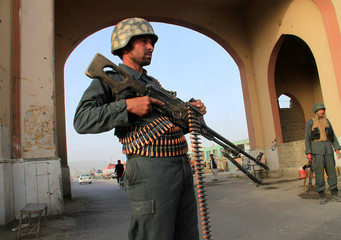 An Afghan policeman keeps watch at a check point in Ghazni city, Afghanistan