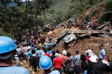 Rescuers search for people trapped at a landslide caused at the height of Typhoon Mangkhut at a mining camp in Itogon