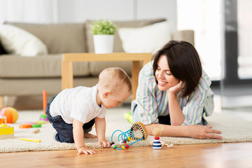 family, child and motherhood concept - happy mother with little baby son playing developmental toys at home