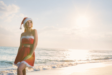 Young beautiful woman in Santa Claus costume celebrates Christmas on a trip to warm countries on the sandy beach