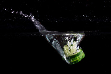 beautiful splash on the water surface from fallen pieces of cucumber in water