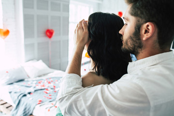 Romantic surprise for your beloved. A handsome man hugs and closes eyes to his girlfriend or his wife making her a romantic dinner in the bedroom for their anniversary or St. Valentine's Day