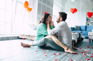Beautiful young tender lovely couple are kissing and hugging each other while sitting on the floor of bedroom with romantic background. St Valentine's day. Anniversary. Date. Love concept