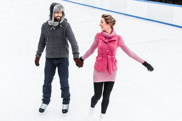 Happy couple holding their hand during ice skating in winter