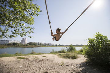 A child is riding on a rope village swing