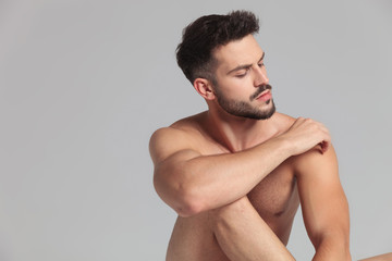 seated naked man with hand on shoulder looks away