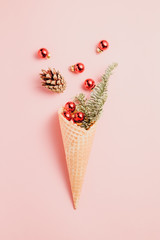 Creative minimalist composition with waffle cone with spruce and Christmas small red balls on a pink background.