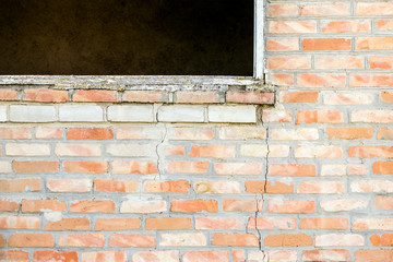 Crack in a brick wall under a window in an empty house. Cracked brick wall in an abandoned unfinished building