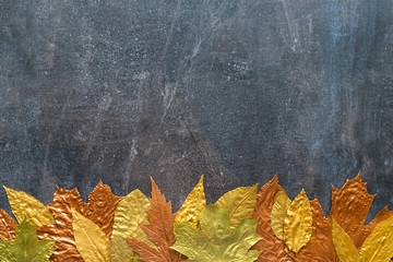 Autumn metallic gold copper leaf frame. Different fall metallic paint leaves on dark natural background with copy space. Horizontal mockup with autumn leaves below