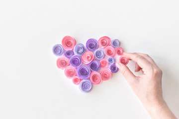 Heart made of paper pink and lilac flowers with woman's hand. Female hand puts a flower in the paper flower heart shape. Handmade, love, romance, gift, wedding, valentines day concept.