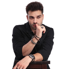 portrait of pensive man in black clothes looking to side