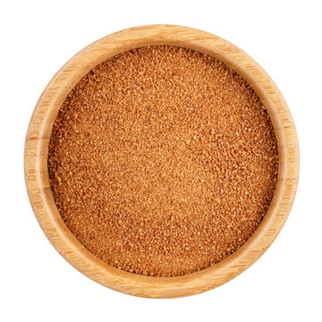 Organic coconut unrefined sugar in wooden bowl isolated on white. Top view.