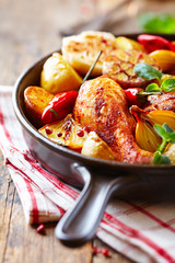 Oven-baked chicken with vegetables and fresh herbs. Homemade food. Symbolic image. Concept for a tasty and hearty dish. Rustic wooden background.
