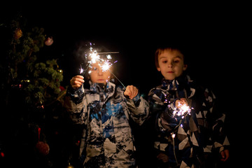 Preschool children, holding sparkler, celebrating new years eve outdoors