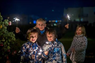 Preschool children, holding sparkler, celebrating new years eve outdoors