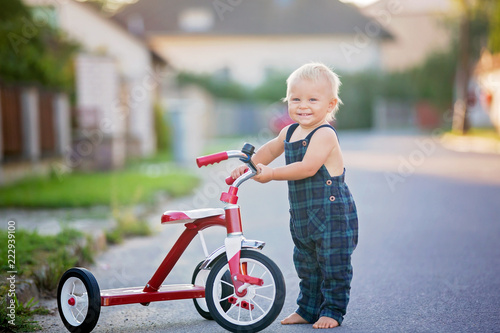 462dbe4adab Cute toddler child, boy, playing with tricycle on street, kid riding bike on