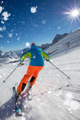 Skier skiing downhill in high mountains