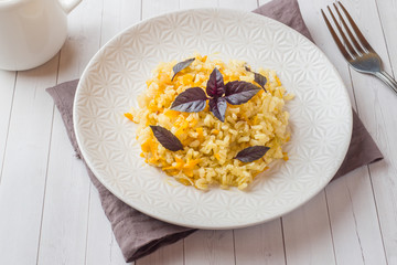 Traditional pilaf, rice with vegetables and fresh Basil in a plate on a light wooden table.