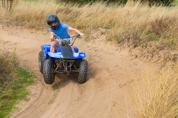 Poster Motorise Young man driving quad through curve