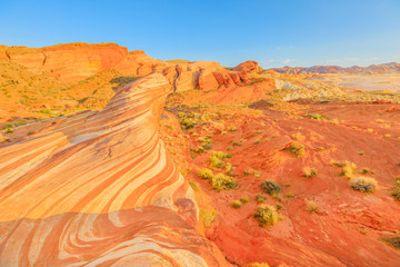 The coloful striped at red sunset of Fire Wave Hike at Valley of Fire State Park in Nevada, United States in Mojave desert landscape. Fire Wave is one of the most iconic formations at Valley of Fire.