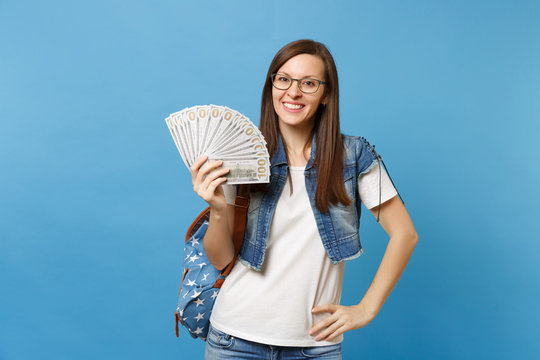 Portrait of young beautiful smiling woman student in glasses with backpack holding bundle lots of dollars, cash money isolated on blue background. Education in high school university college concept.