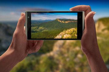 The mountain landscape on a screen of smartphone