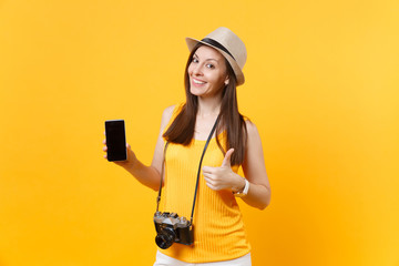Traveler tourist woman holding mobile smart phone with blank black empty screen isolated on yellow orange background. Female traveling abroad to travel on weekends getaway. Air flight journey concept.