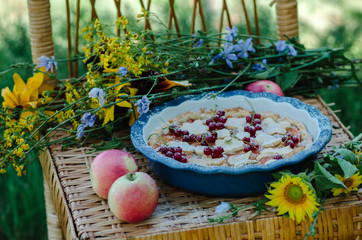 Pie with apples and berries in ceramic form on a wicker stool in the nature