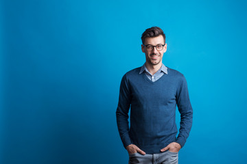 Portrait of a young man with glasses in a studio on a blue background. Wall mural