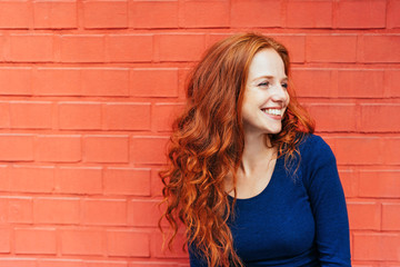 Happy woman with red hair looking to the side