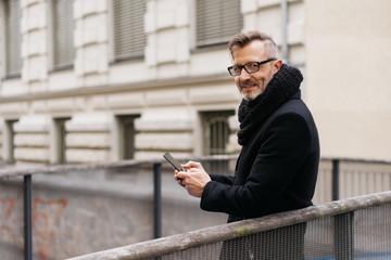 Businessman in overcoat standing on a bridge