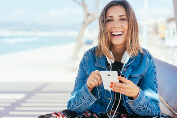 Vivacious laughing young woman listening to music