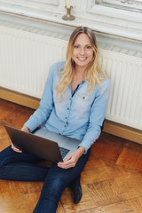 Smiling woman using laptop while sitting on floor