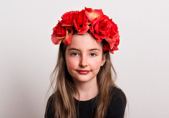 A close-up of small girl with flower headband sitting in a studio.