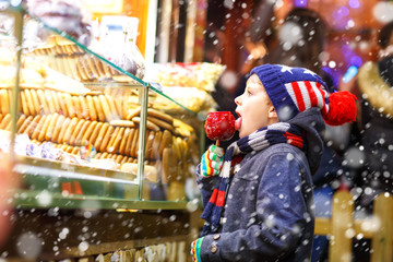 Happy child eating on apple covered with red sugar on Christmas market
