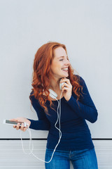 Laughing woman looking to side while holding phone