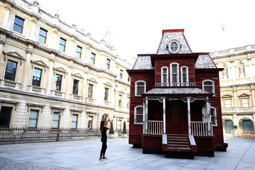 A visitor takes a photo of artist Cornelia Parker's work 'Transitional Object (Psychobarn)' which is on display at the Royal Academy of Arts in London