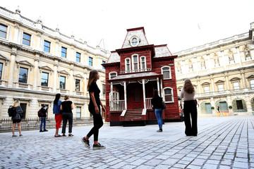 Visitors look at artist Cornelia Parker's work 'Transitional Object (Psychobarn)' on display at the Royal Academy of Arts in London