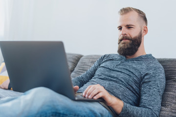 Young bearded man relaxing using a laptop