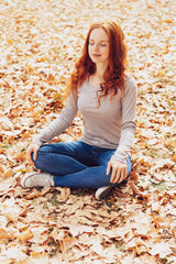 Young woman relaxing on autumn leaves in park
