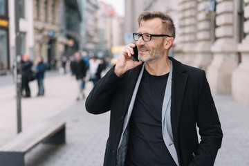 Mature man with mobile phone standing in street