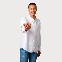 Young african american man presenting and inviting to come with hand. Happy that you came on grey background