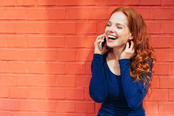 Laughing woman holding smart phone to her ear