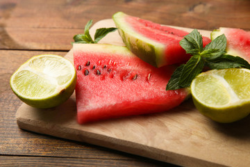 Fresh watermelon with mint and lime on wooden background.
