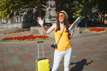 Traveler tourist woman in orange heart glasses with suitcase, city map, retro vintage photo camera spreading hands in city outdoor. Girl traveling abroad on weekend getaway. Tourism journey lifestyle.