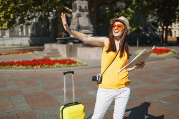 Joyful traveler tourist woman in orange heart glasses with suitcase city map waving hand for greeting, meet friend in city outdoor. Girl traveling abroad on weekend getaway. Tourism journey lifestyle.